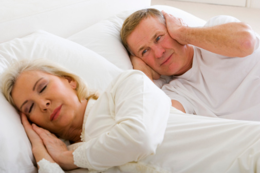 Woman snoring and man covering ears